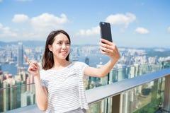 Woman using mobile phone to take photo in Hong Kong Stock Photo