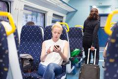 Woman using mobile phone while travelling by train. Royalty Free Stock Photo