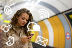 Woman using a mobile phone on the tube underground station, Lond Stock Image
