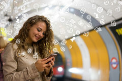 Woman using a mobile phone on the tube underground station, Lond Stock Photo