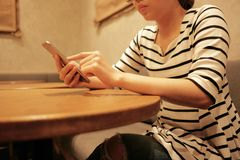 Woman using mobile phone and waiting alone in restaurant background with copy space. Young woman using mobile phone and waiting alone in restaurant background royalty free stock image