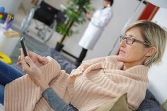Woman using mobile phone while waiting in hospital stock photos