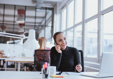 Woman using mobile phone while at work Royalty Free Stock Image