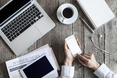 Woman using mobile phone on working table royalty free stock image