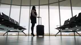 Woman using mobile smart phone at the airport, silhouette voice message, help, assistant, recognition luggage baggage. Woman using mobile smart phone at the stock video footage