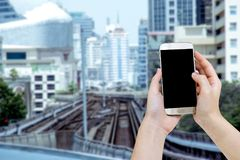 Woman using mobile smart phone with blurry metro background.  stock photography