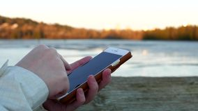 Woman using mobile smart phone. With flowing river background stock video