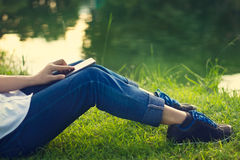 Woman using mobile smart phone on the legs in green grass and lake Royalty Free Stock Photography