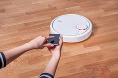Woman using mobile to control robotic vacuum cleaner stock photography