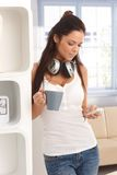 Woman using mobilephone at home. Young woman using mobilephone at home in casual clothing, drinking tea Royalty Free Stock Images