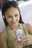 Woman Using Mobilephone While Listening To Music. Happy young woman using mobilephone while listening to music Royalty Free Stock Photography