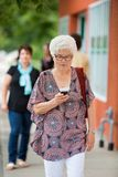 Woman Using Mobilephone On Pavement. Senior women using mobilephone while walking on pavement Stock Photo