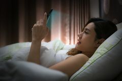 Woman with using modern devices on screen before sleep. Woman with using modern devices on screen before sleep Stock Photography