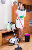 Woman using mop, hoover and dooing housework Stock Image