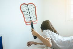 Woman using mosquito swatter at house,Female with mosquito electric net racket in bedroom royalty free stock photos