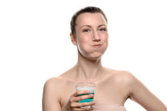 Woman using mouthwash during oral hygiene routine. Healthy happy woman rinsing and gargling while using mouthwash from a glass, during daily oral hygiene routine Royalty Free Stock Image