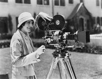 Woman using movie camera outdoors Stock Photo
