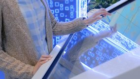 Woman using multimedia touchscreen display of interactive kiosk. Woman hand using interactive touchscreen display of white electronic multimedia terminal at stock footage