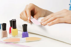 Woman using nailfile. Close up of female hands making manicure Stock Photos