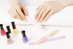Woman using nailfile. Close up of female hands making manicure Royalty Free Stock Image
