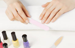 Woman using nailfile. Close up of female hands making manicure Royalty Free Stock Photography