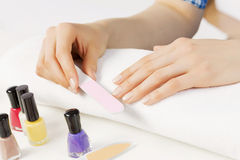 Woman using nailfile. Close up of female hands making manicure Stock Images