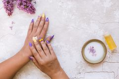 Beautiful woman putting lilac cream on her hand Royalty Free Stock Image