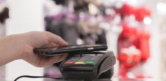Woman using NFC technology for payment in the shop