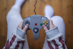 Woman using a Nintendo 64 controller Stock Images