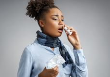 Woman using nose spray. Photo of african american woman in blue shirt on gray background. Medical concept royalty free stock photos