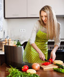 Woman using notebook during cooking Stock Photos