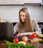Woman using notebook while cooking lunch Stock Images