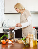 Woman using notebook while cooking Royalty Free Stock Images
