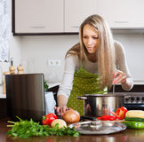 Woman using notebook while cooking soup Stock Photos