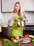 Woman  using notebook while cooking soup Stock Image