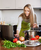 Woman using notebook while cooking soup Stock Photo