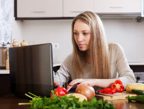 Woman using notebook  at  kitchen Stock Photo