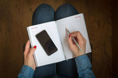 Woman using notebook and phone Stock Images