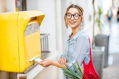 Woman using old mailbox outdoors Stock Photo