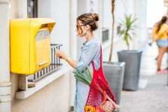 Woman using old mailbox outdoors Royalty Free Stock Photo