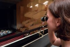 Woman is using opera glasses in a theatre stock images