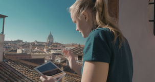 Woman using pad on the balcony with city view stock footage