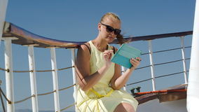 Woman using pad during sea traveling. Young woman in sunglasses using tablet computer while traveling by ship on a windy day stock video