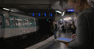 Woman using pad on subway platform. Young woman working with digital tablet in underground. She standing on platform and waiting for the train stock video footage