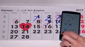Woman using paper calendar and smart phone to synchronize them. VILNIUS, LITHUANIA - NOVEMBER 30, 2016: Woman using paper calendar and smart phone to synchronize stock video