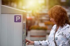 Woman using parking meter royalty free stock photo