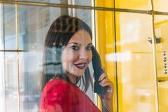 Woman using payphone. Beautiful brunette woman using payphone royalty free stock image