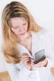 A woman using a pda (2). A pretty woman in a white shirt using a pda Royalty Free Stock Images