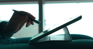 Woman using pen to work with touch pad. Close-up shot of a female hands working with tablet computer using pen to touch screen. She holding tablet PC on the lap stock footage