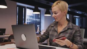 Woman using personal computer and plastic card to making online. Beautiful, concentrated, successful and confident female sitting indoor workplace office with stock footage